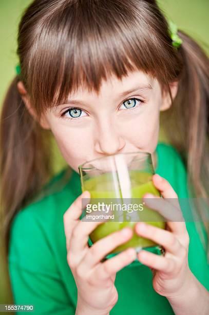 Little girl drinking green juice