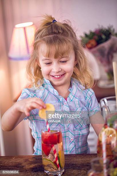 Little Girl Drinking Infused Water with Fresh Strawberries and Lemon