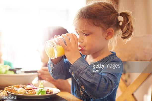 Kleine Mädchen trinkt Orangensaft beim Abendessen