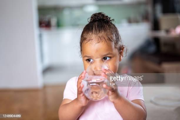 eau potable de petite fille du verre - eau potable photos et images de collection