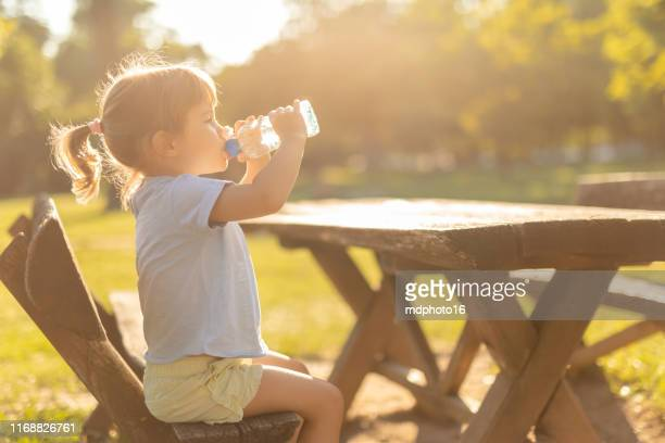 little girl drinking water outdoors - infant with water stock pictures, royalty-free photos & images