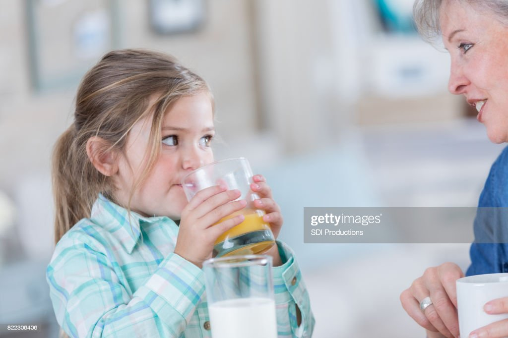 Little girl drinks orange juice with her grandma : Stock Photo