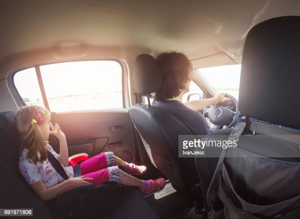 Little girl driving in the car in the backseat