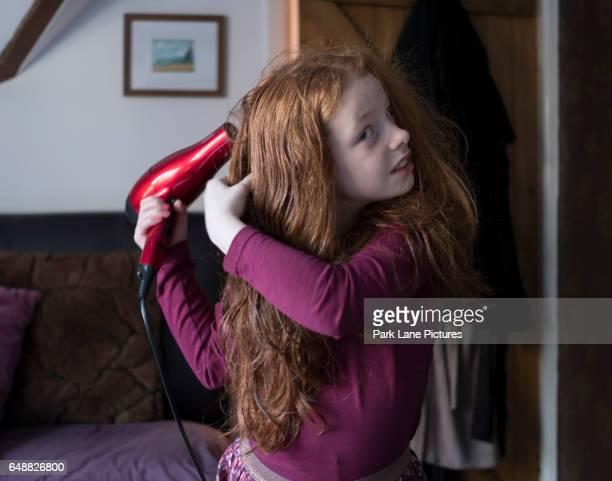 a little girl drying her hair with a hair dryer - strom haare stock-fotos und bilder