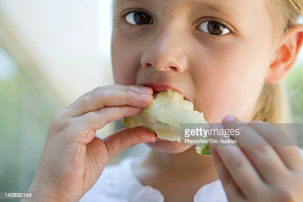 Little girl eatiing apple