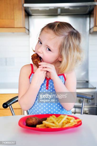 A little girl eating a chicken leg with chips