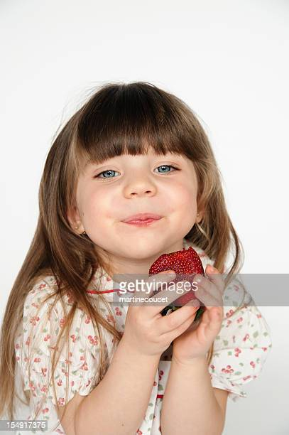 Little girl eating a fresh strawberry.