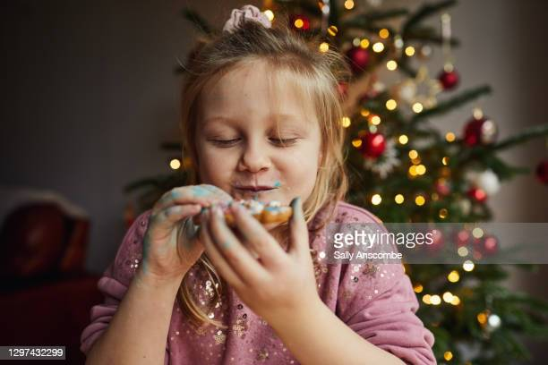 little girl eating a gingerbread - christmas stock pictures, royalty-free photos & images
