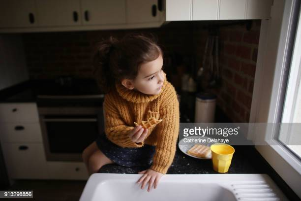 A little girl eating a waffle in the kitchen