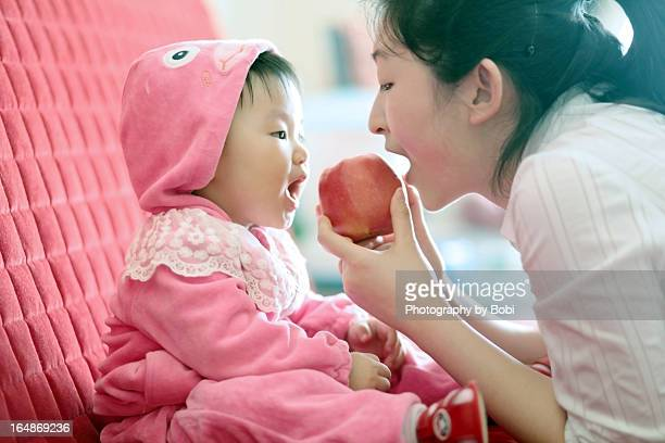 little girl eating an apple with mother