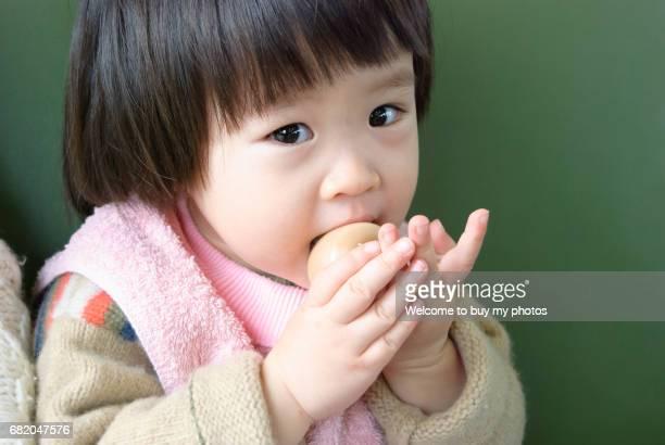 Little girl eating an egg
