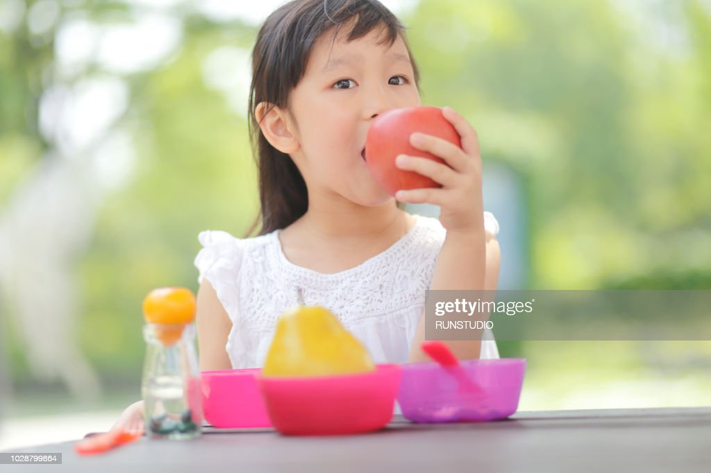 little girl eating apple in park ストックフォト getty images