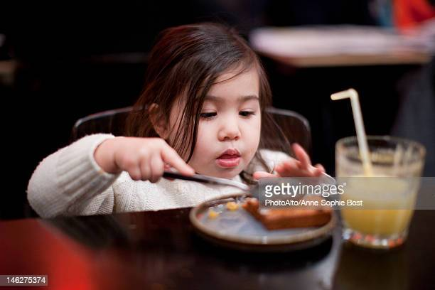 Little girl eating at table