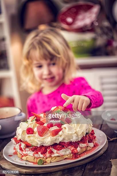 Fillette manger Pavlova de Berry gâteau avec des fraises et framboises