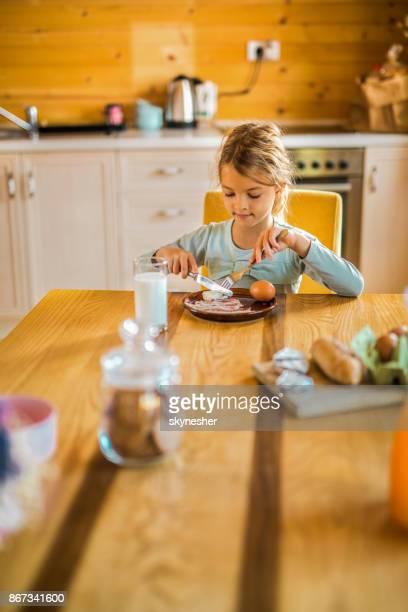 Little girl eating breakfast at dining table.