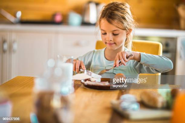 little girl eating breakfast at dining table. - social grace stock pictures, royalty-free photos & images