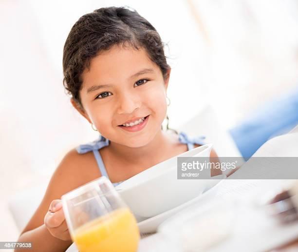 Little girl eating breakfast at home