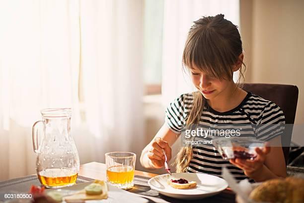 Little girl eating breakfast on sunny morning