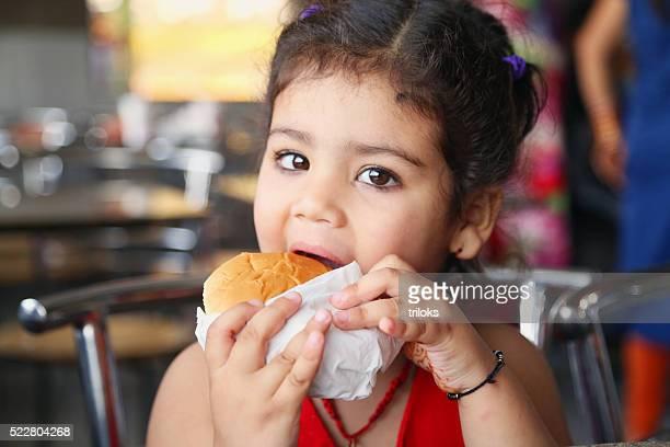 Niña pequeña comiendo hamburguesas