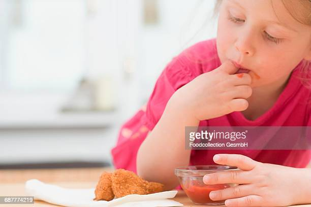 Little girl eating chicken nuggets with ketchup
