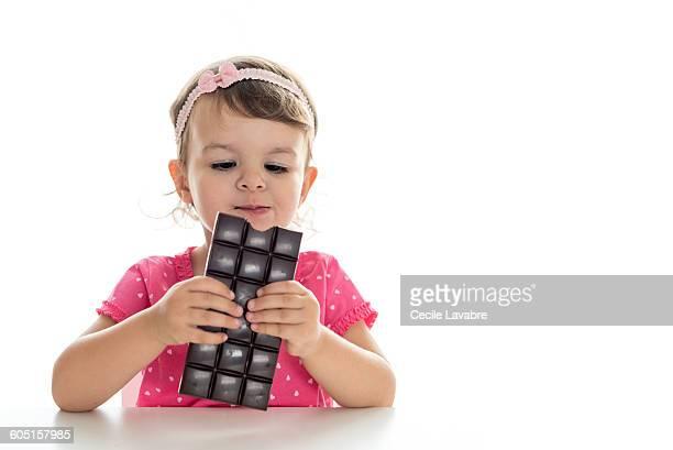 Little girl eating chocolate bar