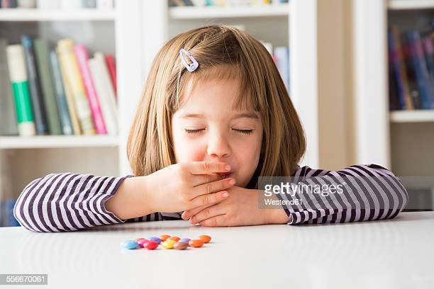 Little girl eating chocolate buttons