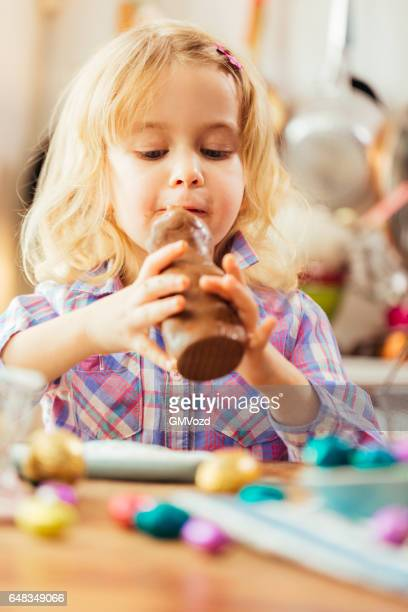 Kleine Mädchen essen Schokolade Osterhasen