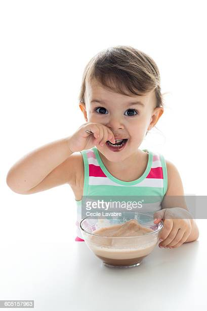 Little girl eating chocolate milk from spoon