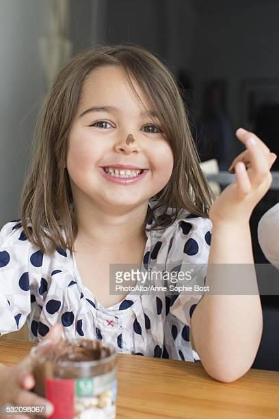 Little girl eating chocolate sauce from a jar with her fingers