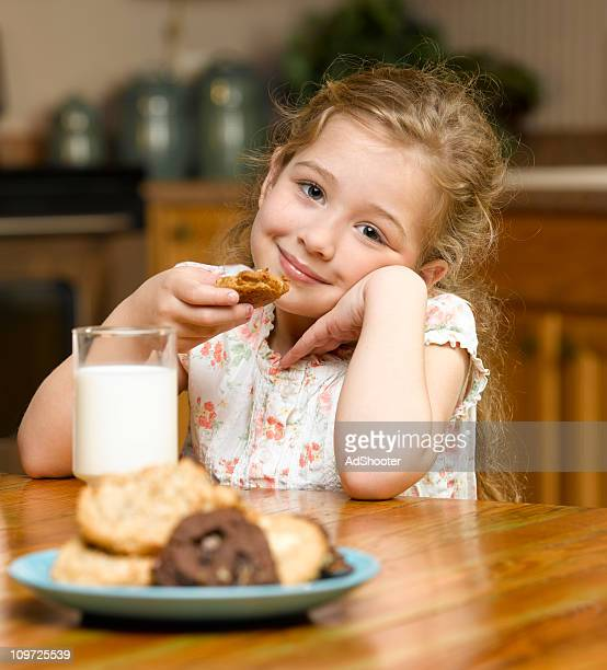 Little Girl Eating Cookies and Milk