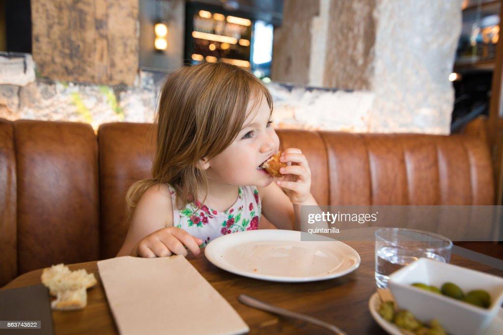 レストランで手でコロッケを食べる少女 : ストックフォト
