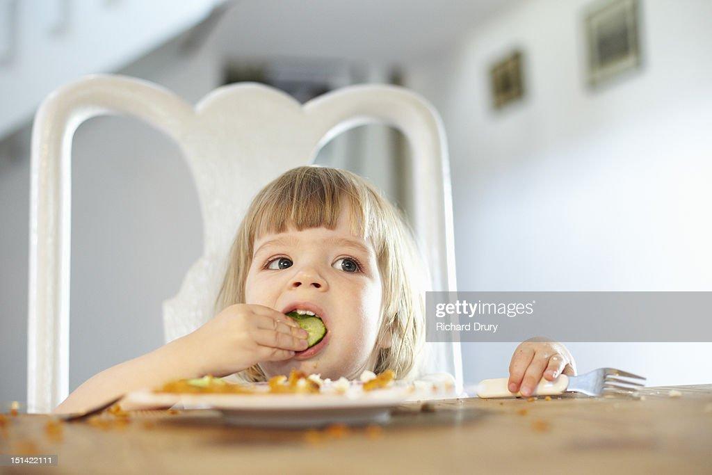 Little girl eating cucumber : Stock Photo