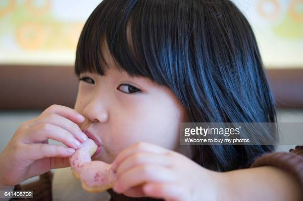 Little girl eating donuts