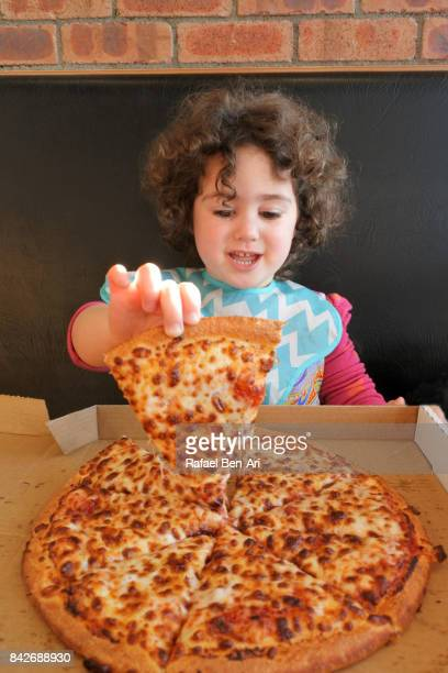 Little girl eating fast food pizza