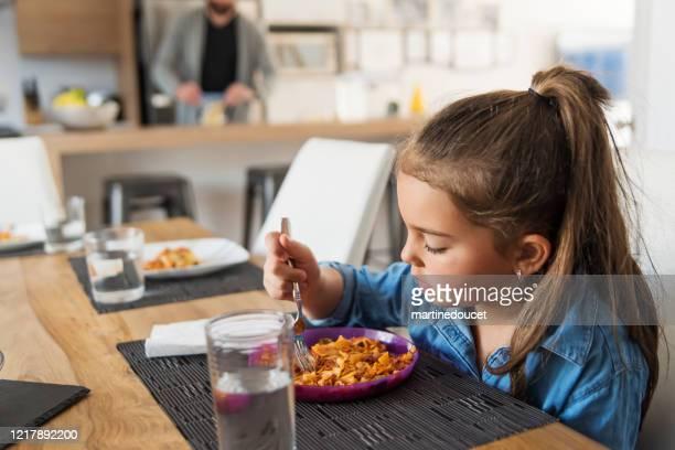 """una niña comiendo su plato a la hora del almuerzo. - """"martine doucet"""" or martinedoucet fotografías e imágenes de stock"""