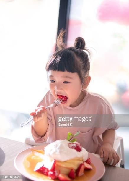 カフェでホットケーキを食べる少女 - 縦位置 ストックフォトと画像