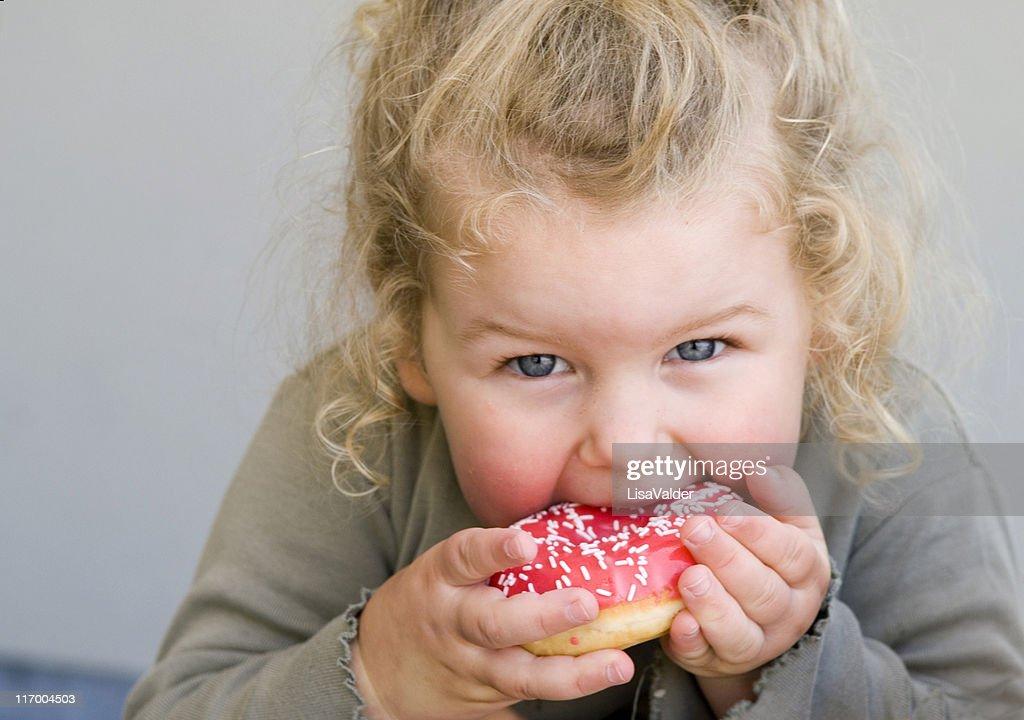 Little girl eating jelly-glazed donut with sprinkles : Stock Photo