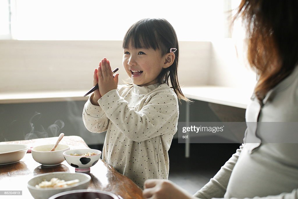 Little girl eating meal,smiling : Stock Photo