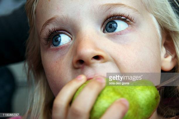 little girl eating pear