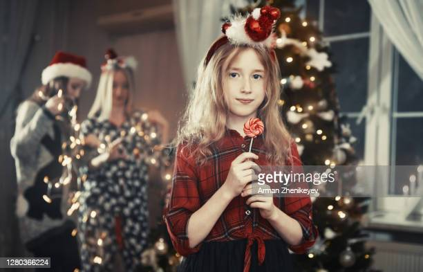 little girl eating peppermint swirl lollipop and her sisters preparing for christmas - mint plant family fotografías e imágenes de stock