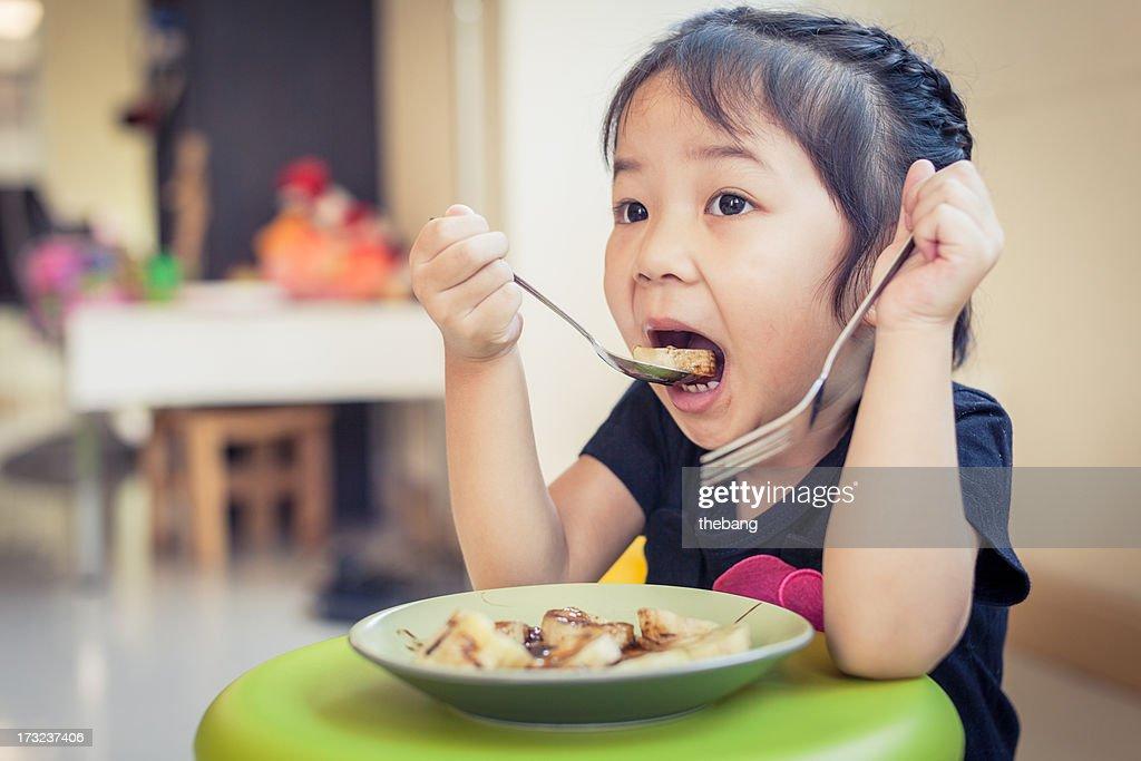 Little girl eating : Stock Photo