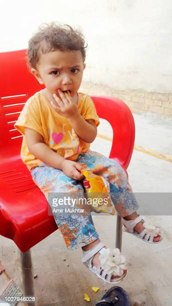 A little girl eating potato chips while sitting on chair
