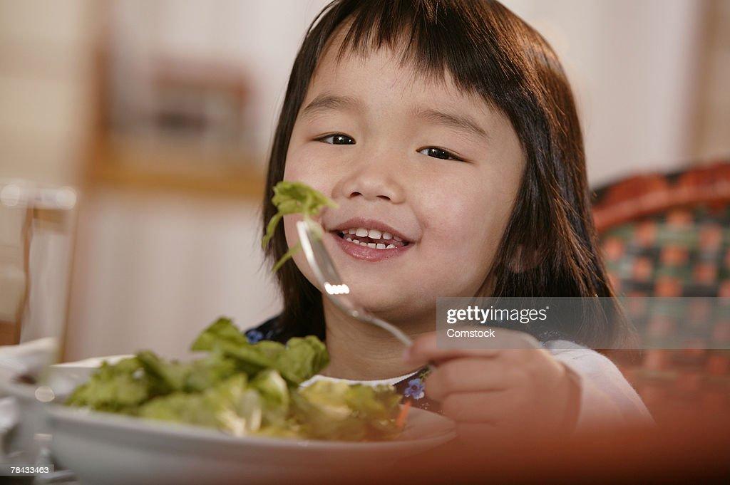 Little girl eating salad : Stockfoto