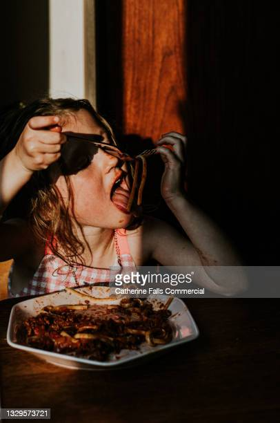 little girl eating spaghetti bolognese in the evening - human joint stock pictures, royalty-free photos & images