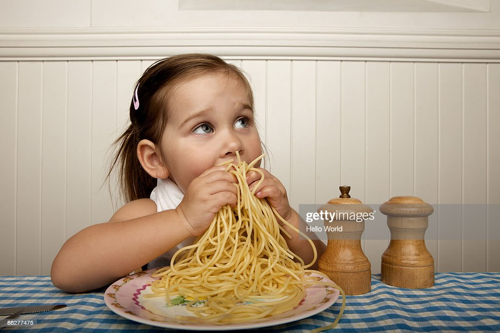 Little girl eating spaghetti with her hands : Stock Photo