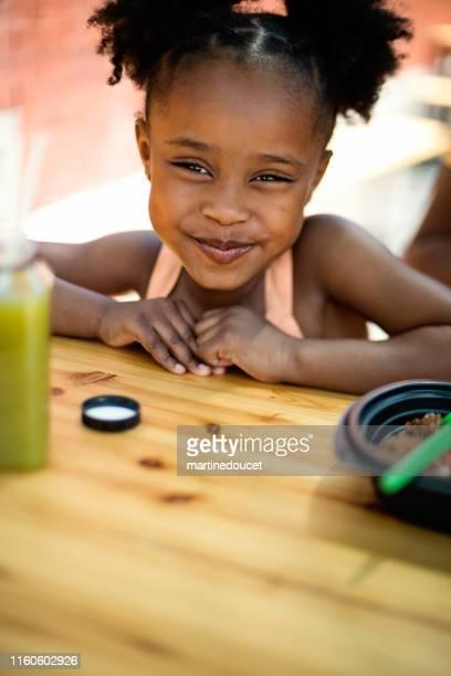 La niña que come saca comida al aire libre.