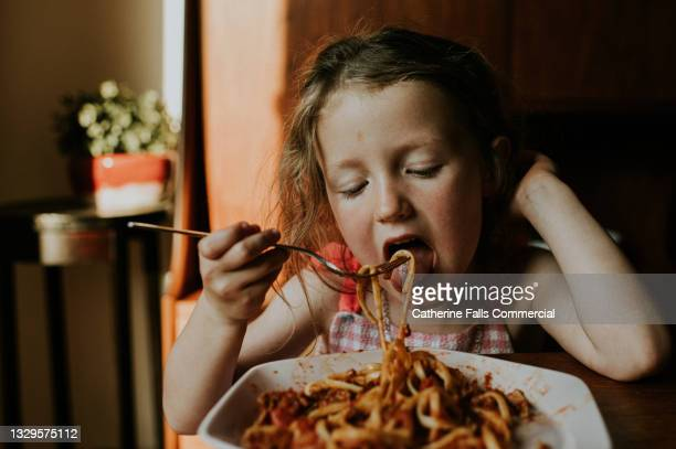 a little girl eats a plate of spaghetti bolognese - human joint stock pictures, royalty-free photos & images