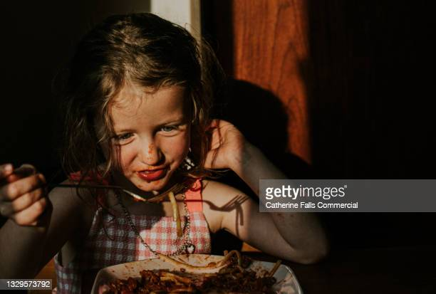 little girl eats a plate of spaghetti - human joint stock pictures, royalty-free photos & images