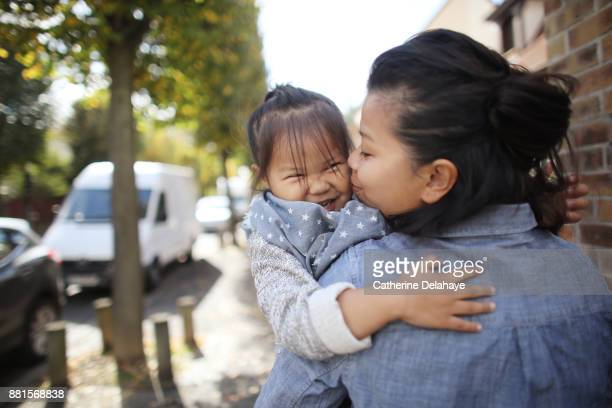A little girl embracing her mum in the street