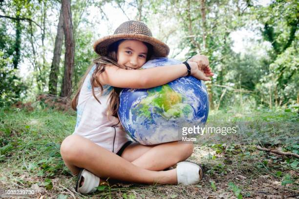 little girl embracing world globe - earth day stock pictures, royalty-free photos & images
